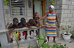 """Reseha Rosier talks with four of her grandchildren on the porch of her house in a model resettlement village constructed by the Lutheran World Federation in Gressier, Haiti. The settlement houses 150 families who were left homeless by the 2010 earthquake, and represents an intentional effort to """"build back better,"""" creating a sustainable and democratic community. Four of Rosier's grandchildren, and their mother and father, live with the older woman."""