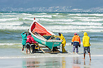 Trek-net fishers launching their small wooden rowing boat into the sea, Strandfontein beach, False Bay, Cape Town, Western Cape, South Africa