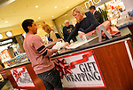 Dec. 12, 2012 - Garden City, New York, U.S. - From right to left, LISA RUIZ, an Assistant Superintendant of the Merrick School District, and ROSEMARY SYREN, the district's Technology Coordinator, help the Merrick Kiwanis Club, a community service group, wrap gifts at Roosevelt Field mall in Long Island, to raise funds to use for charity, during the busy winter holiday shopping season. Some ways Kiwanis helps the community are by providing food, clothing, and school supplies to those in need, sending children to Kamp Kiwanis, providing scholarships and hosting a Harvest Ball for senior citizens.