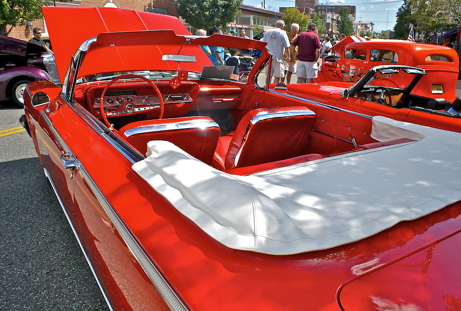 Historic cars including a red Mercury convertable in foreground are viewed by visitors to the antique car show on Main Street, Millville, NJ