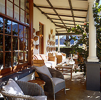 The sun-drenched side veranda or stoep is furnished with wicker sofas and the wall decorated with a collection of baskets