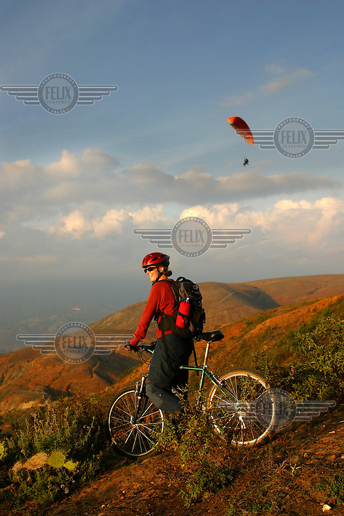 A tourist on a mountain bike in the Andean mountains, while a paraglider sails in the background. Local guides offer a host of activities to tourists, and tourism has become an important source of income in this area.