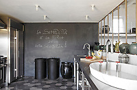 Stainless steel work surfaces and a slate wall define the enclosed kitchen which has been laid with a hexagonal ceramic tiled floor