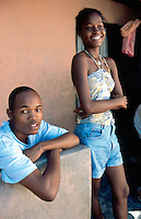 Haiti. Province of Ouest. Port-Au-Prince. Slum of Campeche. Densely populated area. Daily life for a jobless family. Informal economy. The mother has set up at her home's entrance a small shop in order to make some money to feed her family. Brother and sister.  © 2003 Didier Ruef