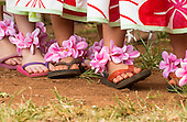 Girls wearing local style rubber slippers and pink plumeria anklets before a hula performance in Hale'iwa, North Shore, O'ahu.
