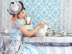 Beautiful asian lady in a luxurious blue dress sitting at a table and pouring tea ina cup. Tea party hostess.