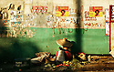 PORT-AU-PRINCE, HAITI - JANUARY 26, 2006: A Haitian vendor sells her vegetables under a wall adorned with various campaign posters for upcoming Haitian elections in the Haitian capital, Port-Au-Prince January 26, 2006.  The National election, now scheduled for February 7, 2006, has some 35 candidates vying for President, and hundreds more running for 129 legislative seats.