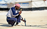 A worker pounds a peg into the ground as he and other workers erect new tents in the Zaatari Refugee Camp, located near Mafraq, Jordan. Opened in July, 2012, the camp holds upwards of 50,000 refugees from the civil war inside Syria. A dramatic rise in the camp population is expected soon. International Orthodox Christian Charities and other members of the ACT Alliance are active in the camp providing essential items and services.