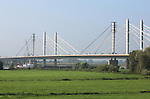 Foto: VidiPhoto<br /> <br /> EWIJK - Heel voorzichtig en nauwelijks zichtbaar voor het blote oog, wordt dinsdag de eerste van vier tuien van de A50-Waalbrug bij Ewijk gevierd. Een unieke klus, die in Europa nog niet eerder is uitgevoerd. De oude brug, die pal naast de nieuwe Waalbrug ligt, wordt op dit moment opgeknapt. Het laatste onderdeel vormt het vervangen van de tuien en het verstevigen van de pilonen. De tuien houden de pilonen op hun plaatst. De vraag is wat er gebeurt als de pilonen aan drie in plaats van aan vier tuien komt te hangen. De aannemers Strukton en Ballast Nedam kunnen de veiligheid van het werk niet garanderen, maar zijn door opdrachtgever Rijkswaterstaat en de rechter deze zomer gedwongen het werk aan de tuien te hervatten. Eind 2015 moet de brug klaar zijn.