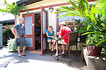 Paia Inn on the North Shore of Maui.  This hotel is located in a  quiet beachfront community and has a private entrance to Paia Bay. Guests having breakfast outdoors in the courtyard.