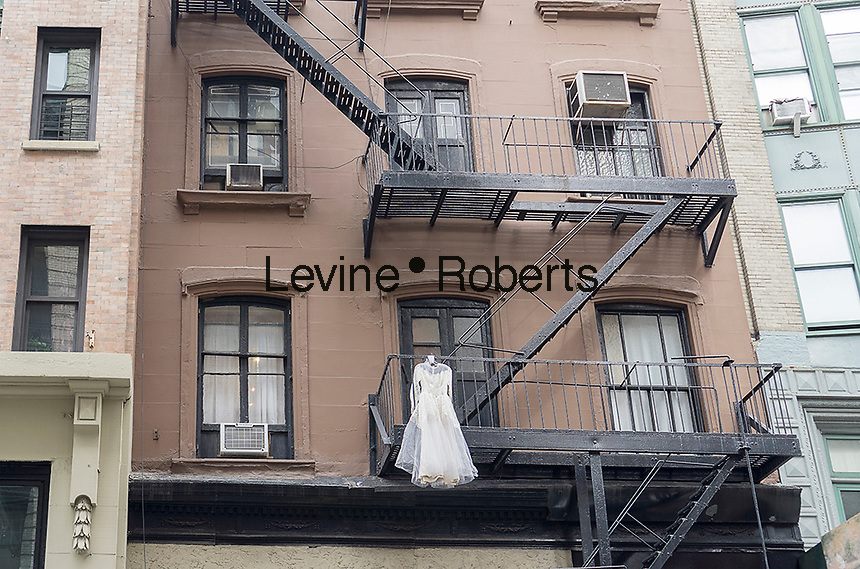 A wedding dress hangs from a fire escape of a tenement in New York on Saturday, February 20, 2016. (© Richard B. Levine)