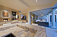 Large sunken wet bar is shown is modern home with windows leading to outside patio