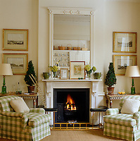 A pair of armchairs, upholstered in green and cream checked fabric, flank the fireplace of this neutrally decorated living room