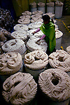 Factory worker inspects barrels of alpaca wool that are packed for shipping in loops to look like rope.  The Bolivians and their ancestors have used the wool of the alpacas to clothe themselves for hundreds of years.  The wool is now shipped all over the world because of its softness and quality of its fiber.