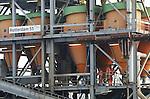 Foto: VidiPhoto<br /> <br /> HETEREN - In de uiterwaarden bij Heteren langs de Rijn wordt in de Plas van Van Wijck volop gewerkt aan de montage van de Rotterdam 55, de zandklasseerinstallatie die de komende tien jaar miljoenen tonnen aan zand en grind gaat verwerken. De huidige plas, met een oppervlakte van ongeveer 20 hectare, gaat de komende jaren 25 hectare groter worden in westelijke richting. De hoofdrolspeler is de Rotterdam 55, een drijvende zandklasseerinstallatie van 88 bij 18 meter en met een hoogte van 16 meter. De 55, zoals het schip wordt genoemd, is een enorme zandfabriek die het afgegraven zand en grind gaat verwerken en wel honderd verschillende zandmixen kan maken, afhankelijk van de wensen van de gebruiker. Het gevaarte wordt gekoppeld aan de Rotterdam 58, een zandzuiger van 60 bij 9 meter. Al het verkochte zand wordt per schip over de Rijn vervoerd. De productie start in februari. Het hele project heeft de naam Randwijkse Waarden gekregen en is in handen van de Dekker Groep, een grondstoffenbedrijf dat ter plaatse een grondwinningsvergunning heeft gekregen voor tien jaar. In ruil voor het af te graven zand en grint, moet het bedrijf het gebied herinrichten als natuur- en recreatieterrein.