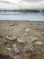 Plastic and other garbage litter the famous Kuta beach on Bali, as surfers enjoy the waves. Enormous amounts of litter wash up every day, especially in the rainy season.