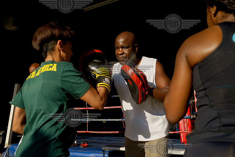 George Khosi training a woman during a corporate boxing day at the Hillbrow Boxing Club. The club relies on a small number of private and corporate clients to pay the club's bills, as much of the work Khosi does is for free.  Hillbrow, in downtown Johannesburg, is the city's most notorious neighbourhood. It is overcrowded, ridden with illegal squats and suffers from high levels of crime much of which is related the thriving illicit drug trade. Against this backdrop, George Khosi's story is not atypical. A childhood spent on the streets, where he survived by committing petty crime and hustling, led to imprisonment at the age of 16. Because he was big and looked older than his age this incarceration was in an adult institution. Here he began to fight since, as he says 'they wanted to make me a woman and I didn't want to be a woman.' When he got out, he took up boxing in earnest. His prospects as a professional boxer looked bright until he was shot and left for dead during a burglary. He lost his right eye and now walks with a limp. His boxing career seemed over but George picked up his gloves again, this time to teach Hillbrow's youngsters. His gym became a place of hope and discipline for local youth, keeping them of the streets and even producing some national champions.