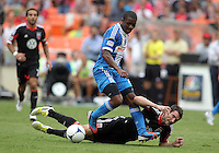 WASHINGTON, D.C. - AUGUST 19, 2012:  Chris Pontius (13) of DC United crashes to the ground after a tackle by Michael Lahoud (13) of the Philadelphia Union during an MLS match at RFK Stadium, in Washington DC, on August 19. The game ended in a 1-1 tie.