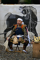 A seated participant during ceremonies at the Somanakamura shrine, Somanomaoi Festival, Minami-soma City, Fukushima Prefecture, Japan, July 26, 2013. During the four-day-long Somanomaoi Festival members of old samurai families ride horseback through the town in traditional armour.  They also take conduct ceremonies at local shrines, take part in horse races, and compete on horseback to catch a flag launched into the air by fireworks.