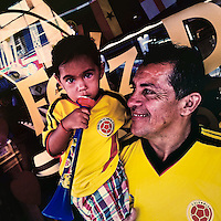 A Colombian father holds his baby girl, both wearing the national football team t-shirt, on the street in Cali, Colombia, 28 June 2014.