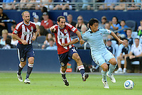 Sporting KC midfielder Roger Espinoza(pale blue) holds off the challenge from Chivas USA's Nick LaBrocca... Sporting KC and Chivas USA played to a 1-1 tie at LIVESTRONG Sporting Park, Kansas City, Kansas.