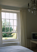 A light and airy country bedroom with a view over the garden