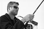An unshaven man wearing sunglasses holds a fishing pole near Puget Sound, Washington.