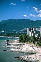 Crowds on Sunset Beach at low tide, on summer bank holiday, in the West End of Vancouver, with Stanley Park and the mountains of North Vancouver in the background.