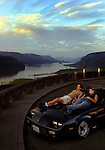 Jacob Sentzsch and Karen Lewallen  take in the sunset and view atop her car at Crown Point along the Columbia River east of Portland, Oregon. The scenic highway road is popular with drivers, motorcyclists and bicyclists due to the dramatic views and curvy roads.