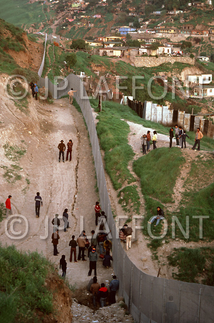 Tijuana, Mexico. January, 1983.<br /> At the border of Tijuana and San Diego, people are gathered on both sides, talking with eachother.