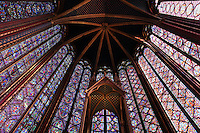 View from below of the choir of the upper chapel of La Sainte-Chapelle (The Holy Chapel), 1248, Paris, France. The upper chapel has four bays and a seven section choir. In the choir, the windows have only two lancets. Fifteen huge mid-13th century windows fill the nave and apse. La Sainte-Chapelle was commissioned by King Louis IX of France to house his collection of Passion Relics, including the Crown of Thorns and is considered among the highest achievements of the Rayonnant period of Gothic architecture. Picture by Manuel Cohen