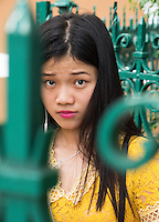 Surprised Vietnamese Girl in Saigon or in Vietnamese Ho Chi Minh City street life where old and new architecture mix in harmony. The bustling Metropolis of South Vietnam.