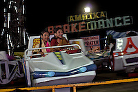 Two girls enjoy a fair ground ride in Mahim next to the Dharavi slum, the fair sets up for a week a couple of times a year with thousands of Dharavi residents flocking to the fair for laughs and thrills.