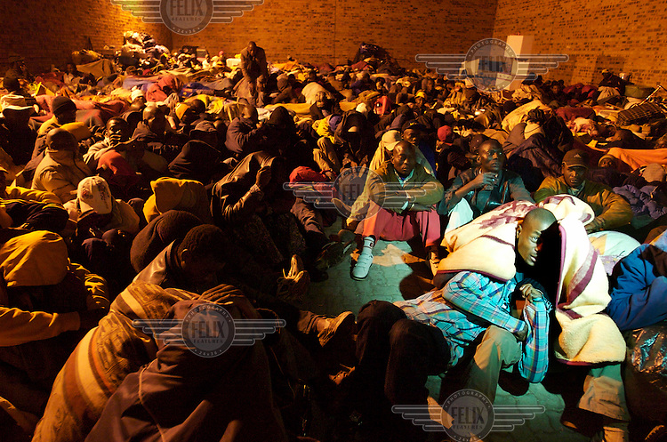 Hundreds of foreigners seek refuge in a parking lot at the Alexandra Police Station shortly after attacks on foreigners began. Thousands of migrants have been forced to flee due to brutal xenophobic attacks on foreign African migrants living in South Africa's impoverished townships.