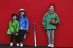 Family, brother and sisters posing after game, smiling, hamming it up in front of camera in front of red wall, Seattle, Washington State USA   MR