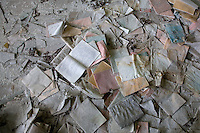 Exercise books and broken glass on a classroom floor.<br />