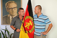 Daniel Helbig (right) and Guido Sand were performers in the East German State Circus and now co-own the DDR Ostel in Berlin which tries to recreate an atmosphere similar to that in East Germany before the fall of the Berlin Wall. They pose in their office with a portrait of Erich Honecker, former East German president, and the flag of the DDR (East Germany) as part of the &quot;commie-kitsch&quot; asthetic of the hostel.