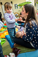 A mother breastfeeding her baby at a drop-in breastfeeding support centre while talking to her older daughter.<br /> <br /> Image from the &quot;We Do It In Public&quot; documentary photography project collection: <br />  www.breastfeedinginpublic.co.uk<br /> <br /> Dorset, England, UK<br /> 17/04/2013