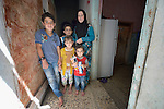 Nahle Al Saye and her four children in the doorway of their apartment in Amman, Jordan. They are refugees from Aleppo, Syria, and received a box of household supplies from International Orthodox Christian Charities, a member of the ACT Alliance. IOCC supports Syrian refugee families in Jordan, as well as many poor Jordanian families that have been negatively impacted by rising rents and prices for basic commodities, the result of the influx of Syrians into the country.