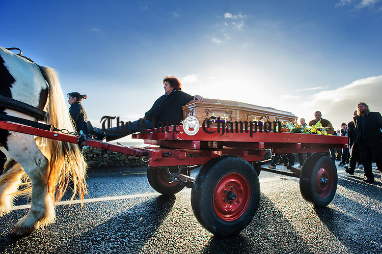 Mrs. Madeleine Dunne sits up with the coffin as Pecker Dunne's remains are taken via horse drawn cart, by family and friends, to the graveyard at Burrane  for burial, following his funeral mass at St. Senan's church Kilrush. Photograph by John Kelly.