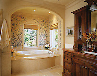 Custom mosaic tub backsplash of flowers, birds, and branches in tumbled stone.