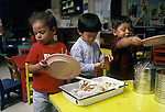 Albany CA Kids, age three, at day care, cleaning up dishes after lunch