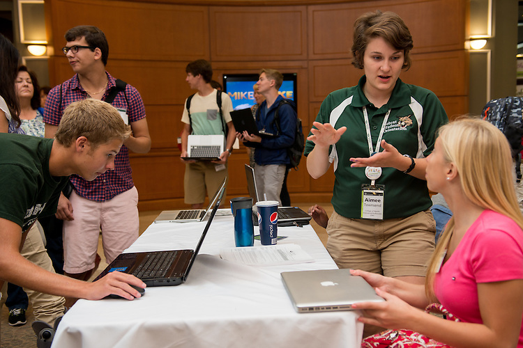 Aimee Townsend, right,  guides incoming freshman through syncing their electronical devises to OU wireless internet during Bobcat Student Orientation check-in.  July 24, 2013.  Photo by Elizabeth Held