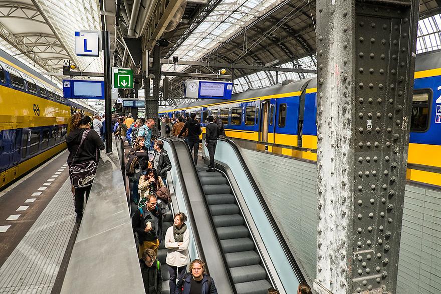 Nederland, Amsterdam, 30 mei 2015<br /> NS-sation Amsterdam Centraal. Trein staat gereed op het perron, in en uitstappende reizigers op de roltrap.<br />  <br /> Foto: Michiel Wijnbergh