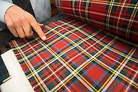 Il proprietario del negozio sfoglia i campionari di tessuti tartan e ne indica uno. The owner of the shop with th different tartan tissues