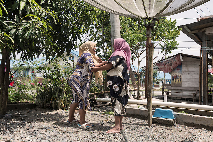 "Indonesia – Sumatra – Aceh - Padang Seurahet - 31-year-old Fawzia (left) laughing in the courtyard of her house with her 37-year-old sister Yessi Kemala Dewi (right). The day of the tsunami, Dewi was invested by a wall of water while she was running for her life together with her sister. A cabinet carried by the water hit her, trapping her leg and preventing them from fleeing. ""I told Fawzia to let me go and save herself, but she wouldn't leave me"" she continues. Today Yessi and Fawzia run a successful sewing business thanks to a Swiss NGO who provided them with 3 sewing machines. The experience of the tsunami has created a special bond between the two sisters who have become inseparable."
