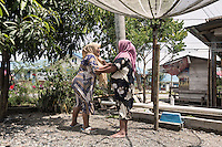 """Indonesia – Sumatra – Aceh - Padang Seurahet - 31-year-old Fawzia (left) laughing in the courtyard of her house with her 37-year-old sister Yessi Kemala Dewi (right). The day of the tsunami, Dewi was invested by a wall of water while she was running for her life together with her sister. A cabinet carried by the water hit her, trapping her leg and preventing them from fleeing. """"I told Fawzia to let me go and save herself, but she wouldn't leave me"""" she continues. Today Yessi and Fawzia run a successful sewing business thanks to a Swiss NGO who provided them with 3 sewing machines. The experience of the tsunami has created a special bond between the two sisters who have become inseparable."""