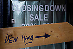 "Wooden Den Haag sign, with ""closing down"" sale behind"