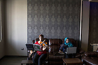 Mojan practices her violin while her mother checks her Facebook page on a laptop.