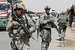 Staff Sgt. Dave Wichman, 39, of Seneca, Kan., and Spc. Sebastian Mutchler, 26, of Latham, N.Y., two soldiers with police mentor team Crazy Horse, take up rear security during a patrol of the Maiwand district bazaar in Kandahar province, Afghanistan. Aug. 8, 2008. DREW BROWN/STARS AND STRIPES